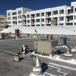 Roofers apply sealing to flat rooftop