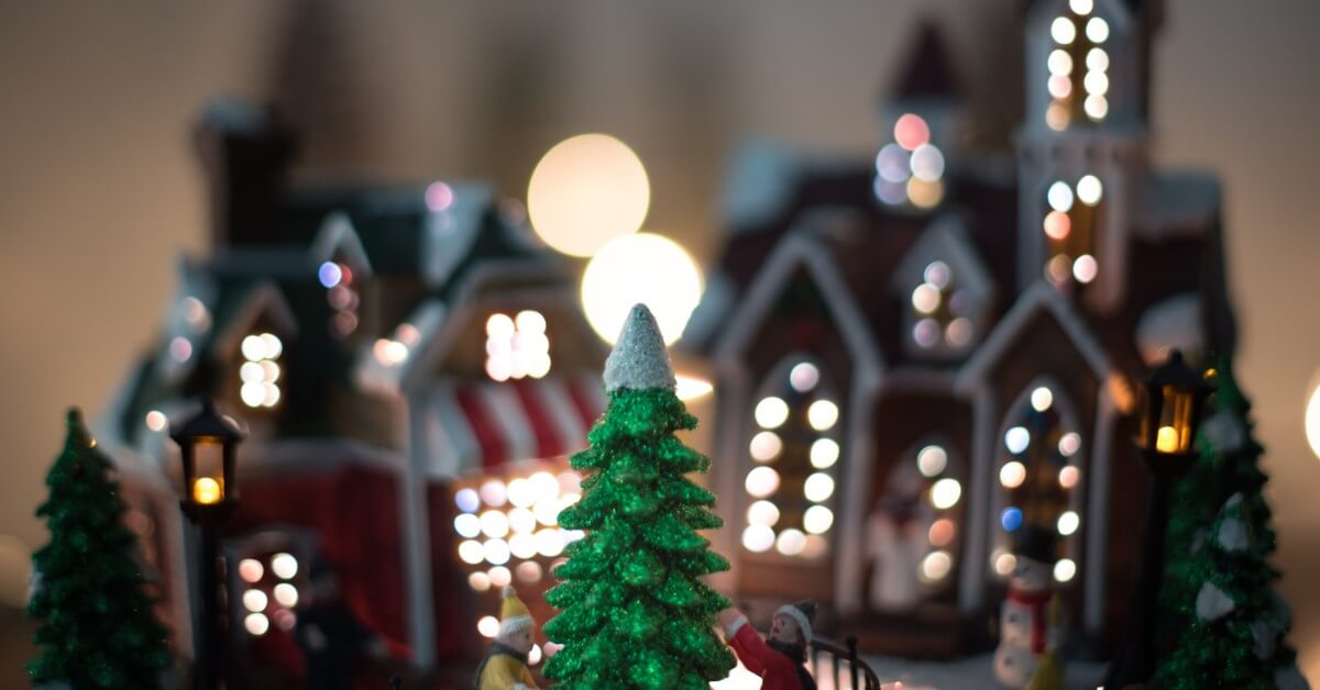Figure of christmas tree in front of cottages