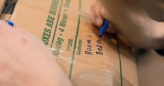 A person packing a box to be moved by PNW Movers