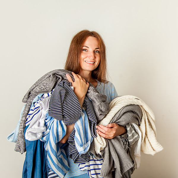 Image of a young woman carrying several clothing items in her hands