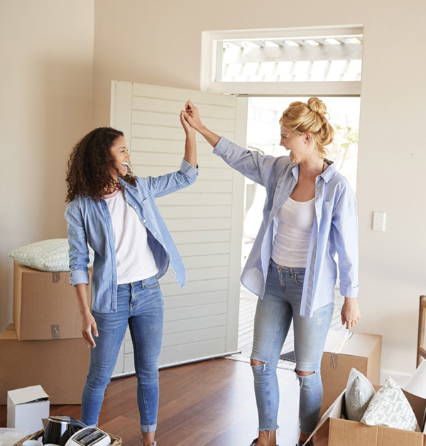 Image of two young women looking happy as they move into their new home