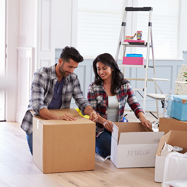 An image of a young couple unpacking boxes in their new home