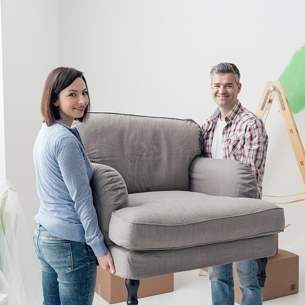 Image of a couple moving a large chair