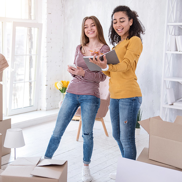 Image of two young women surrounded by moving boxes in an apartment