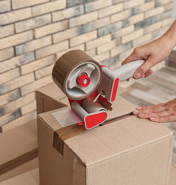 Image of someone taping up a cardboard moving box