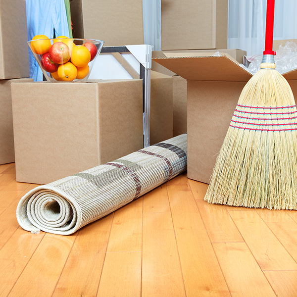 An image of several moving boxes, a broom and a bowl of fruit