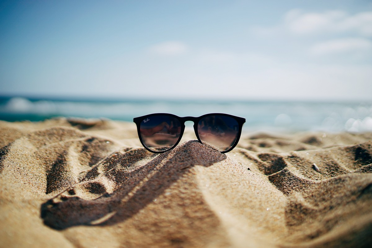 relax in summer with black sunglasses on a sand beach