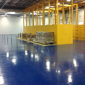 Blue epoxy floors in warehouse with yellow shelving