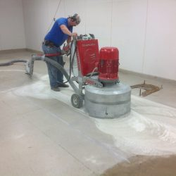 Man using grinder to sand down floors