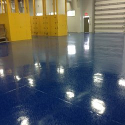 Empty warehouse with blue epoxy floors and yellow shelves