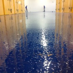 Blue speckled epoxy floors installed by two men in blue shirts