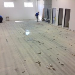 Two men in blue shirts installing new epoxy floors