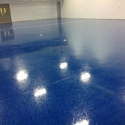 Blue speckled epoxy flooring in empty warehouse