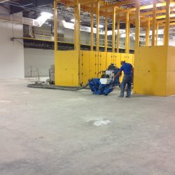 Man in blue shirt installing epoxy floor coating