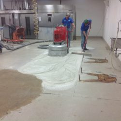 Two men preparing bakery floor for epoxy coating installation