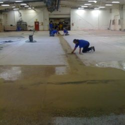 Workers troweling floor before finishing epoxy floor coating