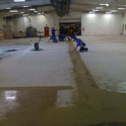 Facility with bare flooring being prepared for epoxy urethane concrete coat
