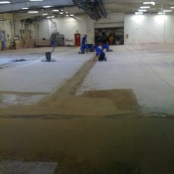 Workers preparing facility for epoxy floor coating