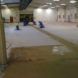 Professionals remodeling epoxy urethane flooring in facility