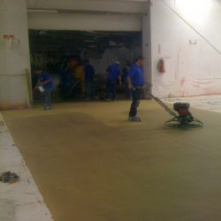 Professionals working on epoxy floor in warehouse
