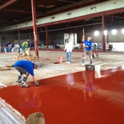 Flooring professionals troweling red epoxy urethane concrete