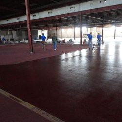 Flooring professionals installing red epoxy urethane concrete