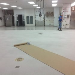Four men installing epoxy flooring in an industrial warehouse
