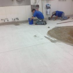 Unfinished epoxy flooring being installed by two men