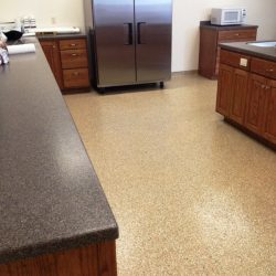 Speckled brown epoxy floors with stainless steel refrigerator