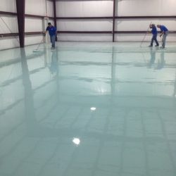 Three flooring professionals installing epoxy urethane concrete floors
