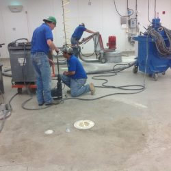 Three men in blue shirts installing concrete floors in unfinished facility