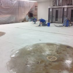 Concrete epoxy floors being installed by two construction workers