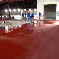 Red urethane concrete broadcasting being installed by professionals