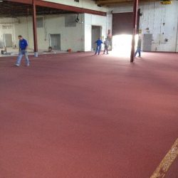Men inspecting red urethane concrete in warehouse