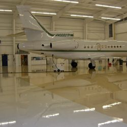Private jet in airplane hangar with reflective epoxy flooring