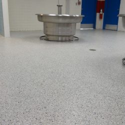 White speckled epoxy flooring in hospital room with hand-washing station
