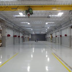 Flooring professional working on epoxy floors in manufacturing building
