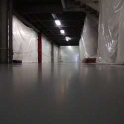 Epoxy floors being installed in hallway with white tarps