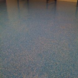 Empty room with blue speckled epoxy flooring