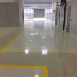 epoxy floors with yellow pathway in empty building