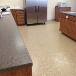 Kitchen with stainless steel fridge, granite counters, and speckled epoxy flooring