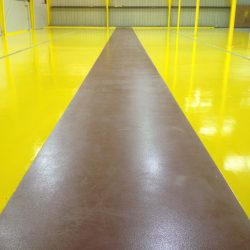 Yellow epoxy floors surrounding brown pathway in empty building