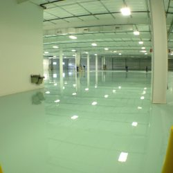 Workers installing epoxy floors in warehouse with two yellow poles