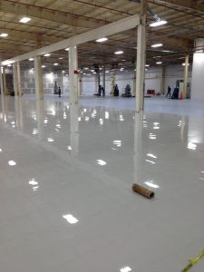 White glossy epoxy floors being installed by flooring professionals