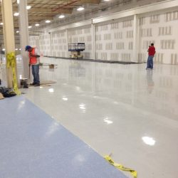 Flooring professionals working on white epoxy floor in empty warehouse