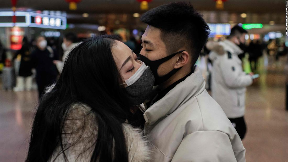 two people kissing with masks on