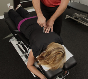 A woman rests on a massage table and receives a treatment