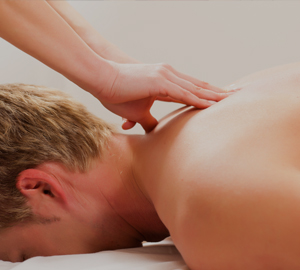 A man's shoulders are massaged by a therapist