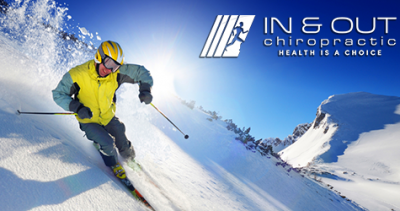 A man skis down a slope, the In & Out Chiropractic logo hovers in the corner