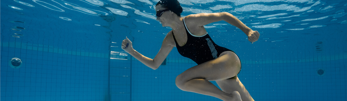 girl in a one piece black bikini jogging in pool